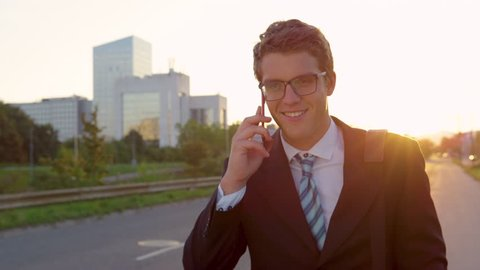 SLOW MOTION, CLOSE UP, LENS FLARE: Golden sunbeams shine on Caucasian yuppie talking on the phone while going home from work. Successful businessman calling home as he walks away from office buildings