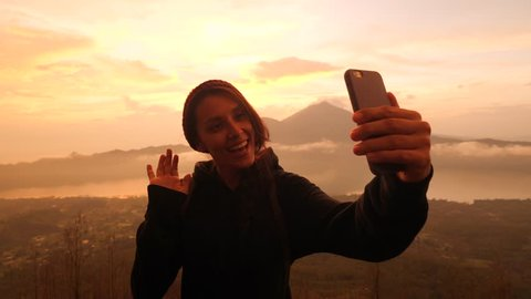 Young Mixed Race Tourist Blogger Girl Recording Selfie Video from the Top of the Mountain Using Smartphone with Beautiful Sunrise on Background. 4K Slowmotion Travel and Freedom Lifestyle Concept Shot