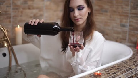 Woman in white shirt pouts red wine in a wine glass taking a luxury bath. Pretty girl enjoying in the bathroom with burning candles.