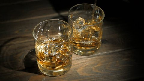 Pouring of scotch whiskey or cognac into glasses with ice cubes on dark wooden background, close up