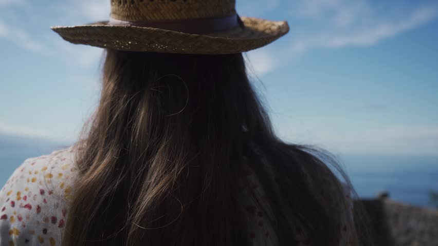 The girl traveler comes up in a dress and a straw hat to the edge of a cliff to look at the blue ocean from above. Recreation and relaxation surrounded by beautiful and quiet nature. | Shutterstock HD Video #1022842783