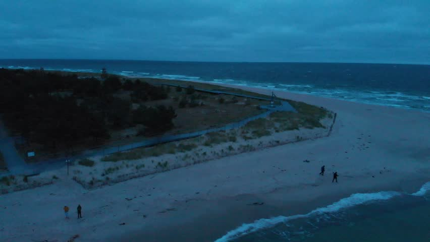 Two pairs of tourist walking at a sandy beach at the very end of Hel Peninsula. Poland, Europe. Aerial pan. | Shutterstock HD Video #1022846743