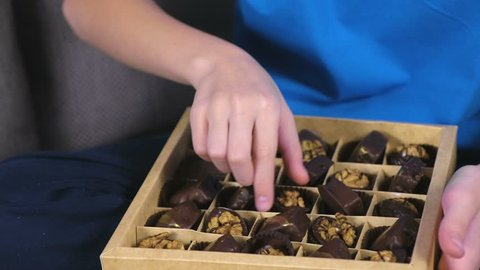 Boy opens a box of chocolate candies and eat cocolates. Close-up chocolates.