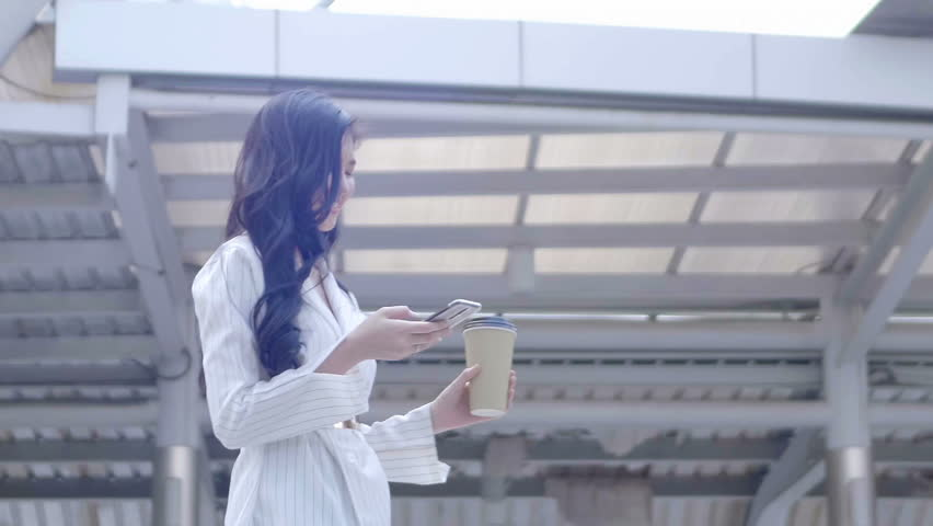 Young Asian businesswoman Using Smart Phone are walking and drinks coffee in city centre Thailand.  communication, everyday life Technology Concept. SLOW MOTION | Shutterstock HD Video #1022861893