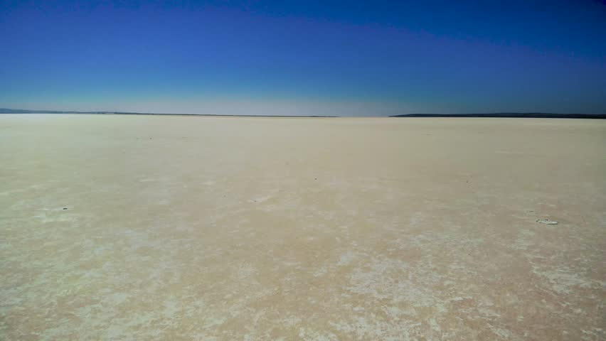 Drone shot of desert salt flats. Aerial of Lake Tuz dried lake bed in Central Turkey. Popular tourist destination of endless sand. Moving forward on flatland toward horizon. | Shutterstock HD Video #1022868403