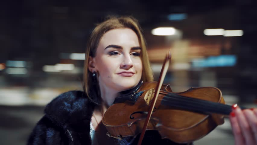 A joyful girl in a black half-length coat is holding a violin in her hands and playing on it in a winter evening in the square in the center of the city. Blurred background. Camera motion to around | Shutterstock HD Video #1022885593