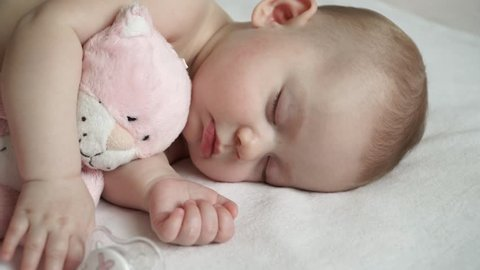Close-up of a cute newborn baby girl sleeping with a soft pink cat toy