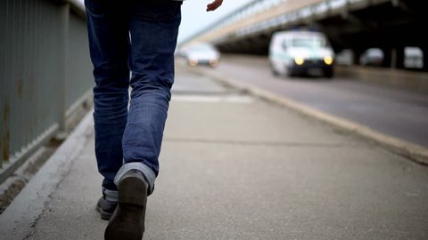 Young Man Wearing Blue Jeans Walking On Bridge. Selective Focus On Legs. Man Alone Concept.