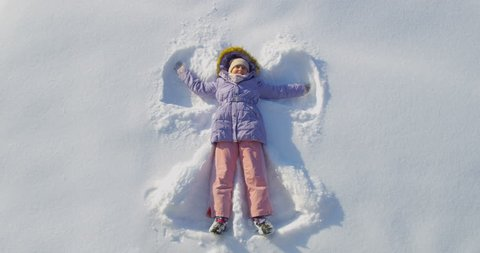 Happy Little Child Girl Laying Down on the Snow Making Snow Angel Shot from Top View on Sunny Day High Angle in Slow Motion Moving Arms and Legs Lying on the Back