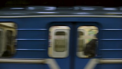 CINEMAGRAPH - Blue subway train with people inside moving fast, view from metro station. Close up for windows of subway train passing fast at underground station