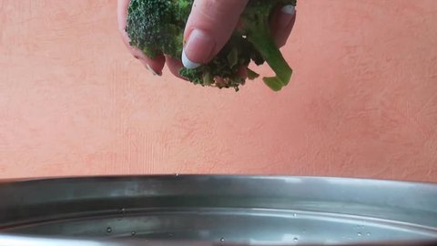 Close-up: cooking broccoli soup. Female hand adds frozen broccoli florets to boiling water.