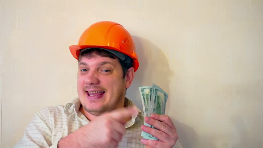 Funny young man in a construction helmet with a stack of hundred dollar bills in his hands | Shutterstock HD Video #1023099343