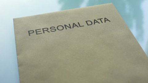 Personal data top secret, hand stamping seal on folder with important documents
