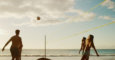 Active friends playing beach volleyball at sunset, cinematic slow motion golden light