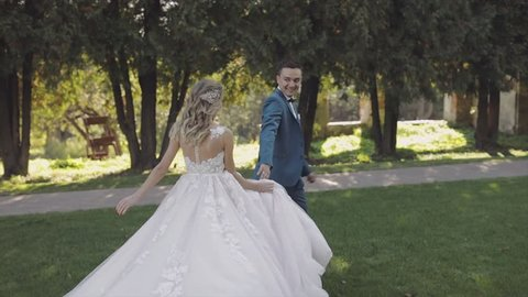 Wedding couple run together in the park. Lovely groom and bride. Wedding day. Slow motion