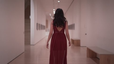 Chinese American Girl in San Francisco living her life pondering and wondering what is happening with an existential crisis. this girl is in a museum walking straight down in a red beautiful dress