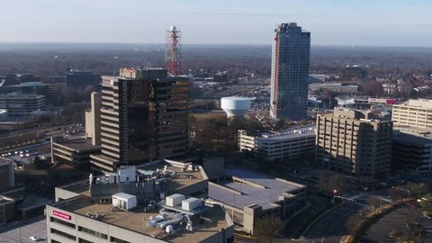 Tysons, VA / USA - December 27 2018: Slow descent while panning left to right across the Tysons Corner skyline, International Drive, and the Galleria parking lot in the morning.