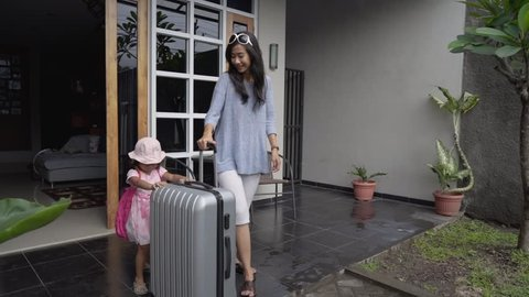portrait of mother put suitcase in the car trunk and her child helped her