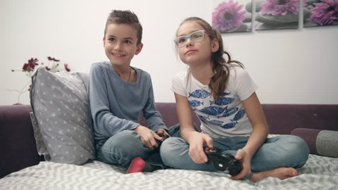 Friends playing video game fight at home. Boy and girl playing video games. Brother and sister enjoy game console. Kids have fun together