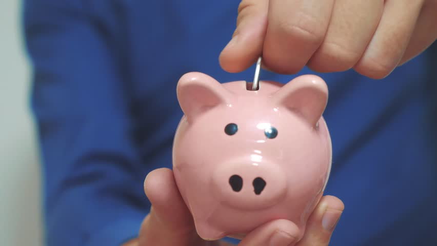 businessman man makes savings puts coins in a piggy bank. piggy bank business concept. slow motion video. saving money is an investment for the future. Banking investment and finance. hand is putting