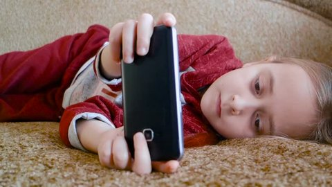 Girl teenager watching a video in the phone while lying on the couch.