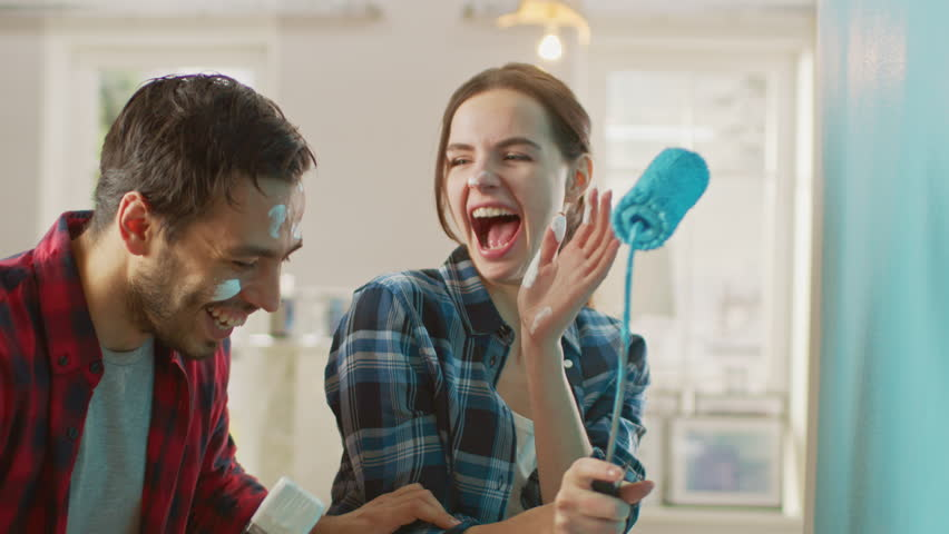 Beautiful Couple Decorate Their New Apartment and Fool Around. Husband and Wife are Painting the Wall with Rollers that are Dipped in Light Blue Paint. They are Happy and Have Fun. Renovations at Home | Shutterstock HD Video #1023187993
