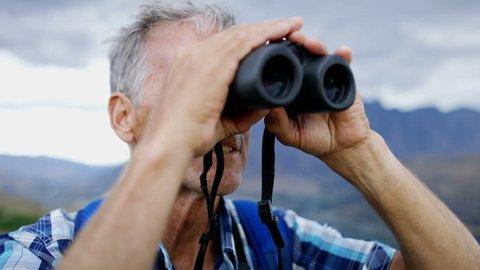 Confident Caucasian senior man traveller with rucksack hiking using binoculars outdoor Mt Aspiring Otago New Zealand RED WEAPON