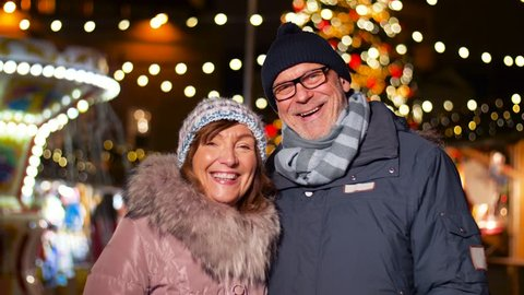 love, winter holidays and people concept - happy senior couple smiling at christmas market on town hall square in tallinn, estonia
