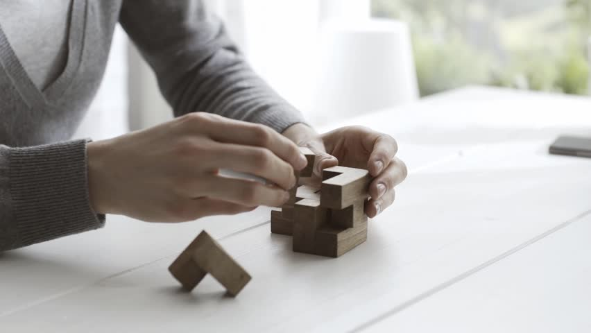 Smart woman playing with an interlocking wooden puzzle, she is trying to solve it   Shutterstock HD Video #1023220243