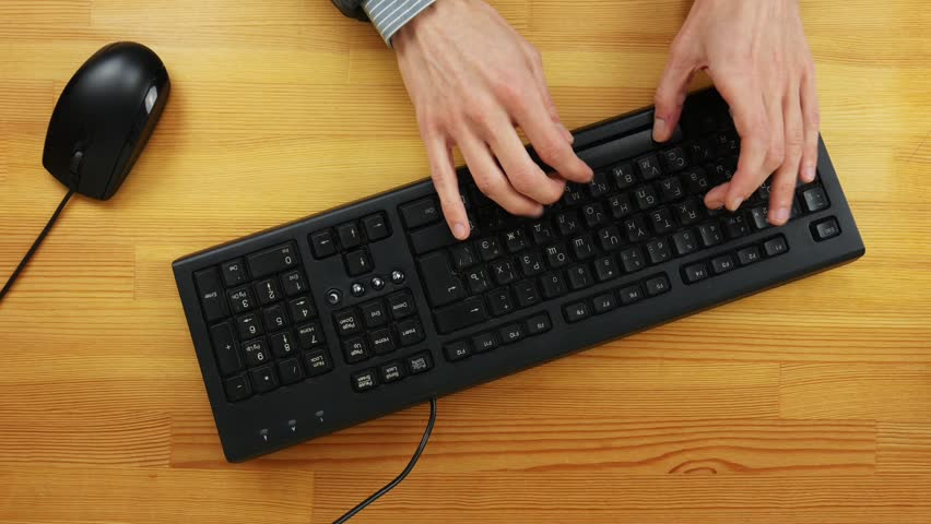 The man in the office typing on the keyboard on a wooden table. Top view | Shutterstock HD Video #1023226423
