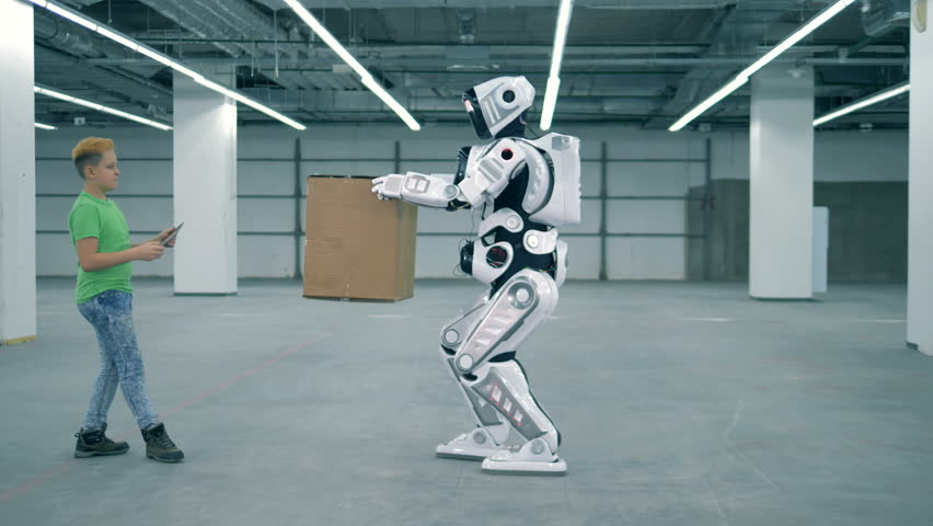 Bionic droid is lifting an carrying a box under teenage boy's supervision | Shutterstock HD Video #1023238903