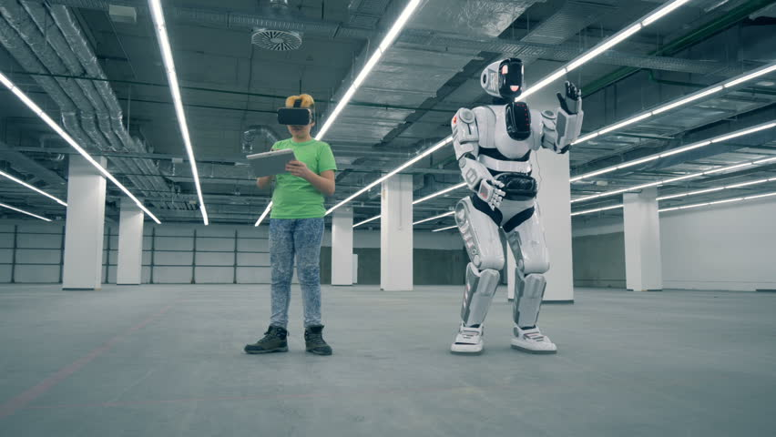 Boy in VR-glasses with a tablet and a robot moving near him | Shutterstock HD Video #1023238933