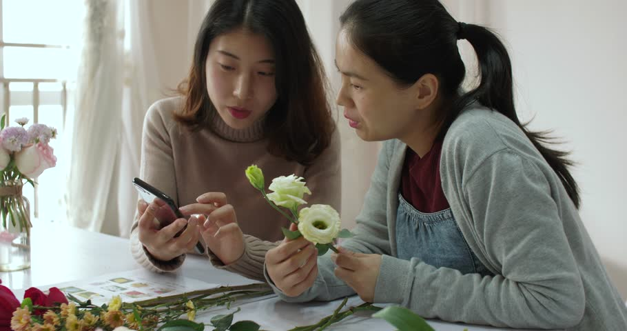 Beautiful chinese florist is using smartphone to show her female student flower information, she is explaining the Characteristics of Platycodon grandiflorum,in chengdu china | Shutterstock HD Video #1023243403
