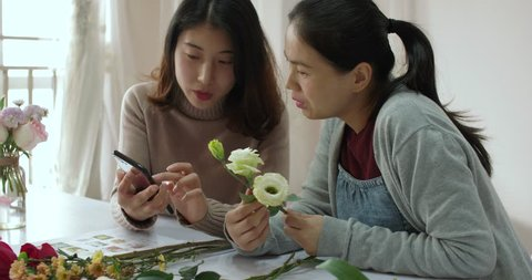 beautiful chinese florist is using smartphone to show her female student flower information, she is explaining the Characteristics of Platycodon grandiflorum,in chengdu china