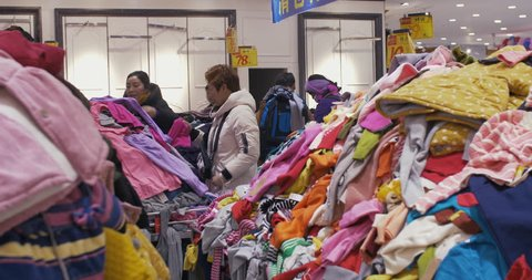 Chengdu, Sichuan/ China-January 29 2019: customer shopping in the discount cloth shop, piles of cloth in the store with low price. many cheap clothing stores at the Hehuachi market.