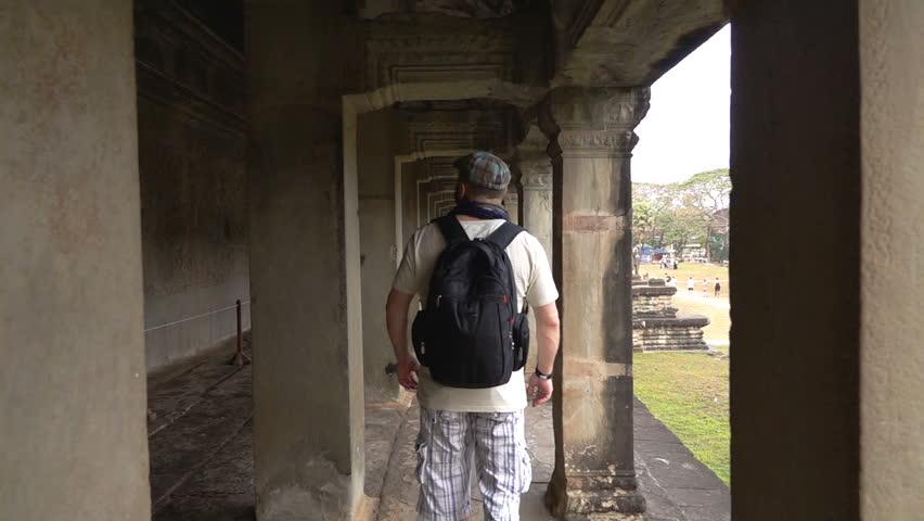 Angkor Wat, Cambodia -NOV 05, 2018: Man walking in ancient angkor and admiring it, slow motion shot at 240fps   | Shutterstock HD Video #1023256243
