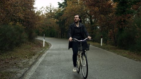 An active Italian man rides his bike down a street surrounded by trees in a rural area in Tuscany, on an overcast day. Wide shot on 8k helium RED camera.