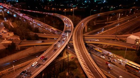 Aerial drone night video of multilevel junction highway crossing during rush hour with heavy traffic