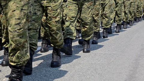 Soldiers with camouflage uniform and black boots marching in formation on parade at national holiday. Special police, guards and army forces on march at anniversary. Independence Day. Slow motion