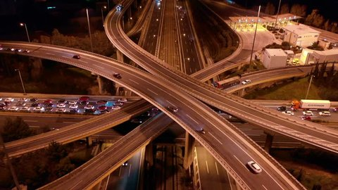 Athens, Attica/Greece - January 29 2019: Aerial drone night video of multilevel junction highway crossing in National road during rush hour with heavy traffic
