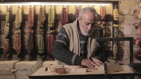 Old man cutting hand made olive soap pieces in Tripoli -Lebanon
