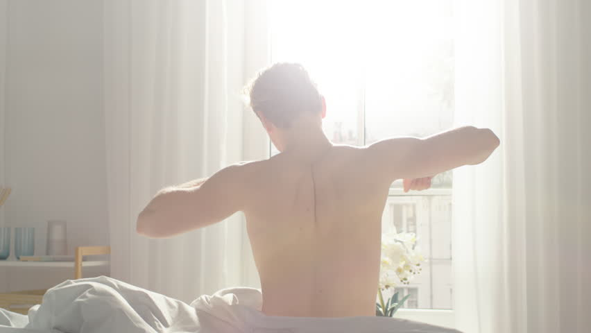 Handsome Fair Boy Sleeping Cozily in Bed, Slowly Wakes up, Gets out of Bed and Stretches Lazily. Young Caucasian Man. Early Morning Sun Shines Through the Window.   Shutterstock HD Video #1023333613