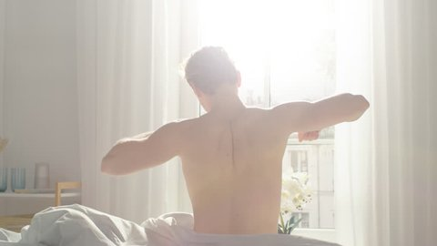 Handsome Fair Boy Sleeping Cozily in Bed, Slowly Wakes up, Gets out of Bed and Stretches Lazily. Young Caucasian Man. Early Morning Sun Shines Through the Window.
