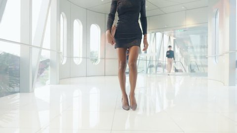 Beautiful slender Asian girl ladyboy walks along a spacious light corridor with stained glass windows. looking at the camera and smiling. Thai transgender model.