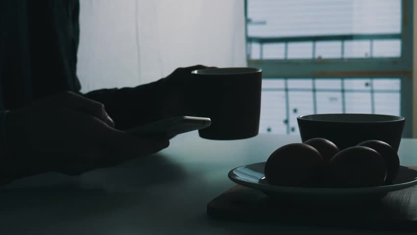 A man sits at the dinner table and holds a smartphone in his hands. Healthy breakfast. Close up | Shutterstock HD Video #1023350263