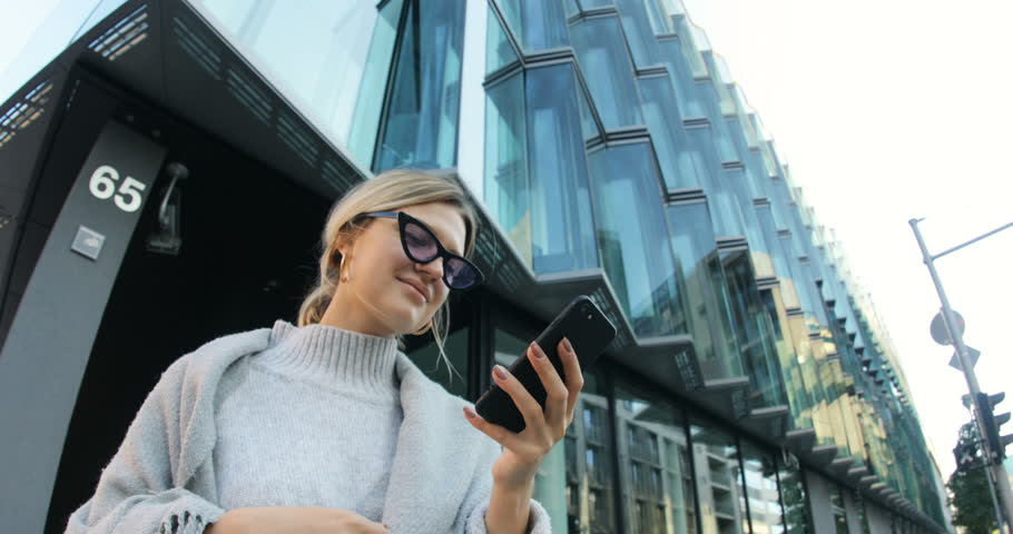 Likable young woman wearing elegant clothes reading message on smartphone, smiling. Portrait of pretty Caucasian girl in purple sunglasses. Modern background. Shot from below. Street.