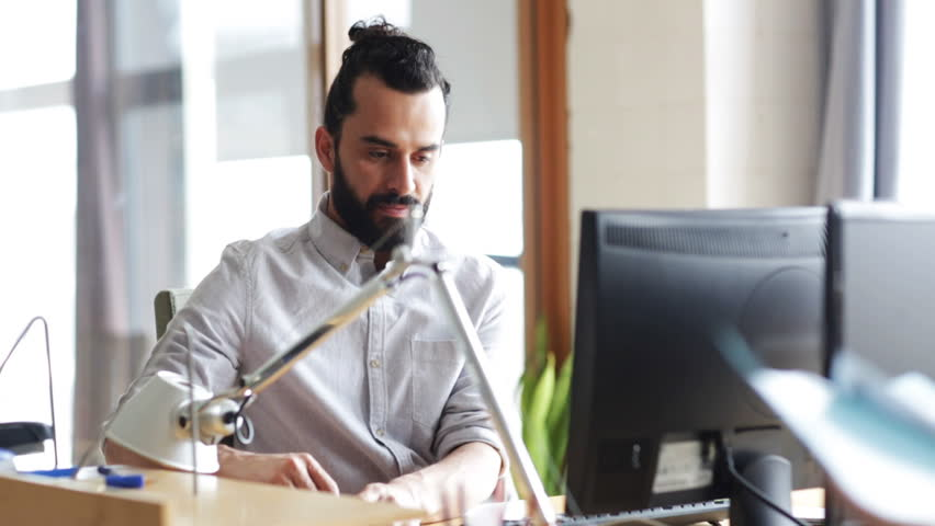business, startup, technology and people concept - happy businessman or creative male office worker with beard working at computer