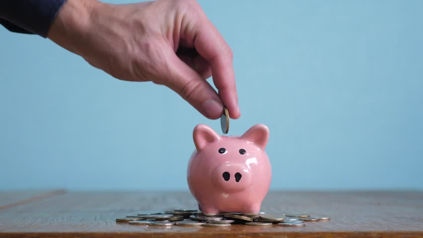 Piggy bank business standing on a pile of coins concept. A hand is putting a coin in a piggy bank on a yellow background. saving money is an investment for the future. Banking lifestyle investment and | Shutterstock HD Video #1023403123