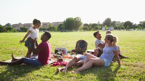 Happy families doing pic-nic in pubblic park outdoor - Young parents having fun with children in summer laughing together outside - Positive mood, parenthood, childhood and food concept