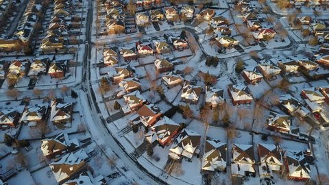Aerial drone footage of a suburban community in Canada after a blizzard snow storm.  Snow fills the field of view and everything is coated in white the sun sets in the distance.